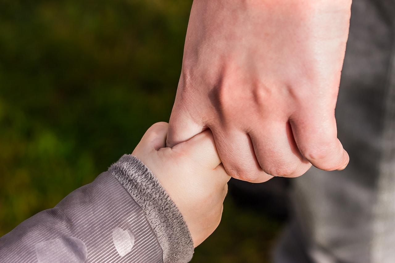 Un enfant tient la main d'un adulte
