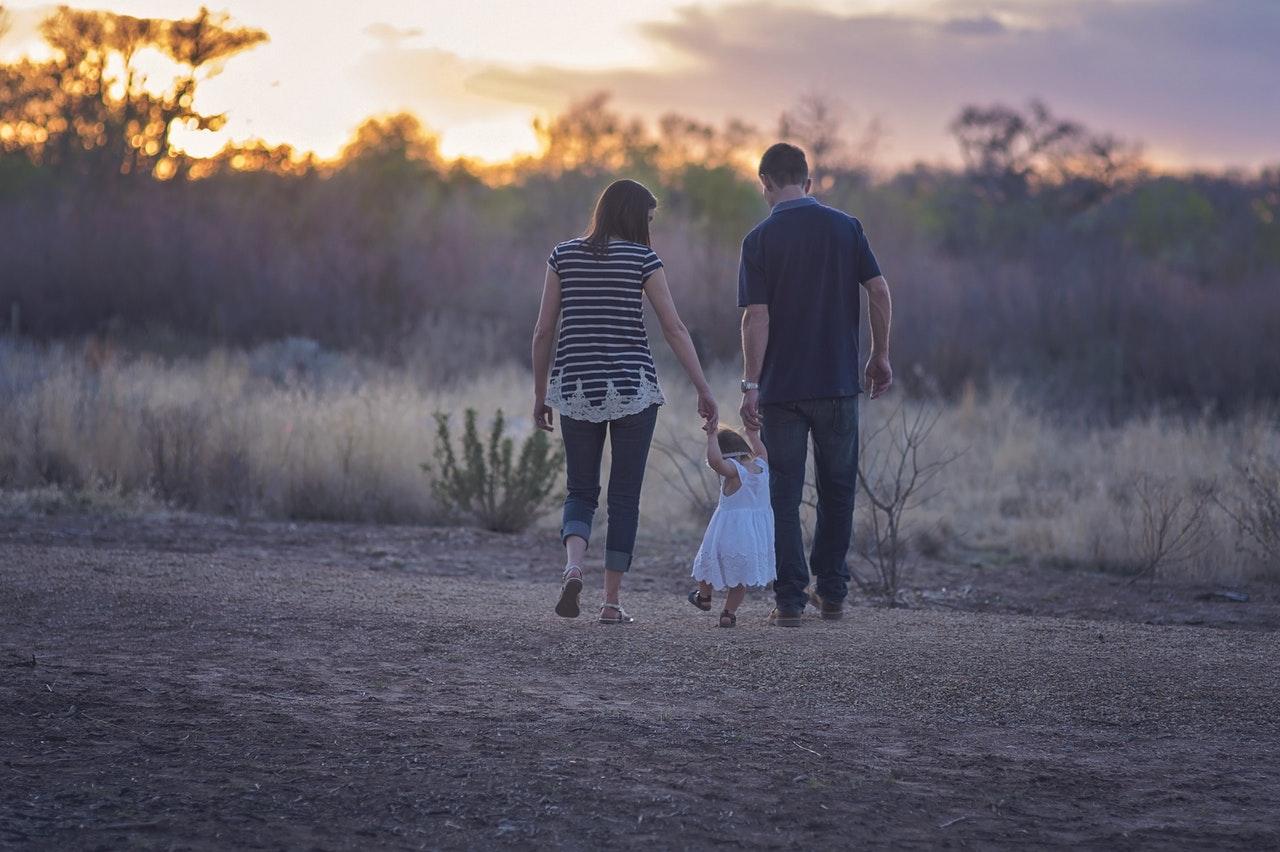 Deux parents et un enfant marchent en campagne