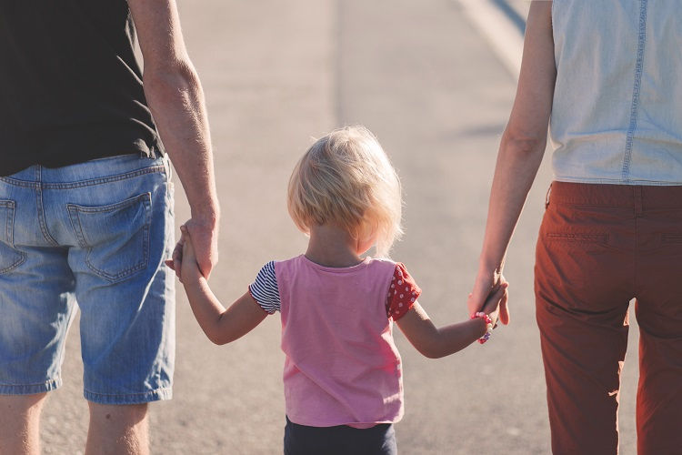 Fillette tiens la main de deux adultes, jour ensoleillé